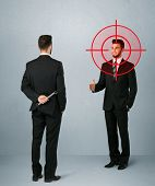 picture of backstabbers  - Ruthless businessman handshake with a hiding weapon and a head target point  - JPG