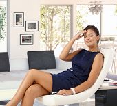 pic of caress  - Attractive young brunette tired caucasian woman in blue dress resting in leather chair at trendy home - JPG