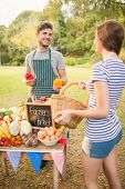 stock photo of farmer  - Brunette buying peppers at the farmers market on a sunny day - JPG