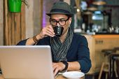 foto of internet-cafe  - Fashionable and stylish young man drinking coffee listening music and internet browsing at the cafe bar. Selective focus. Toned image. ** Note: Visible grain at 100%, best at smaller sizes - JPG