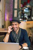 picture of internet-cafe  - Fashionable and stylish young man talking on the phone relaxing with coffee music and internet browsing at the cafe bar - JPG