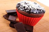 stock photo of chocolate muffin  - Homemade delicious fresh baked chocolate muffins with desiccated coconut in red silicone cups and pieces of chocolate concept for dessert - JPG