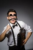 stock photo of moustache  - Young man with false moustache holding case  isolated on gray - JPG