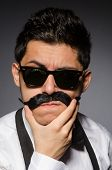 picture of moustache  - Young man with false moustache isolated on gray - JPG