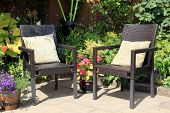 stock photo of lobelia  - Two garden chairs surrounded by shrubs and flowers - JPG