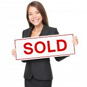 image of real-estate agent  - Real estate agent holding sold sign isolated on white background - JPG