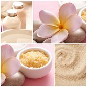 Bottles of SPA cosmetic products and bath salt, pebbles and frangipani flowers