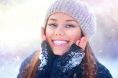 Winter girl portrait. Beauty Joyful Teenage Model Girl touching her face skin and laughing, having f poster