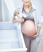 Pregnant woman standing near crib and with love touching her belly, the future mother with tendernes poster