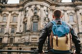 A Tourist Or Traveler With A Backpack Looks At A Tourist Attraction In Berlin Called Berliner Dom. T poster