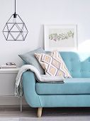Vibrant Sofa Decorated With Cushions And Woolen Plaid, Small Cabinet Under Stylish Lamp In Bright Su poster