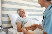 Cheerful senior man lying on bed receiving health care at home. Nurse advising old man on medication poster