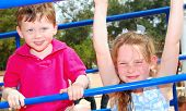 stock photo of swingset  - Cute boy and girl on playground outside - JPG