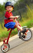 stock photo of tricycle  - Cute young boy wearing safety helmet riding tricycle - JPG