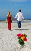 picture of hookup  - Romantic couple walking away from bouquet in beach sand - JPG