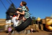 stock photo of tire swing  - Young kids having fun on tire swing - JPG