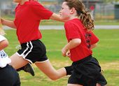 young girl running to make play during soccer game