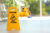 Safety Sign With Phrase Caution Wet Floor And Blurred Mop Bucket On Background. Cleaning Service poster