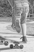 tomboy riding skateboard on sidewalk