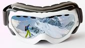 Snowshoeing - reflection in ski goggles - female with racket trekking in snow