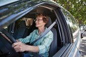 Active senior woman smiling while driving car