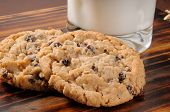 picture of cookie  - Two oatmeal raisin cookies with a glass of milk - JPG