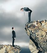 Two Businessmen On Different Cliff Levels Looking At Each Other. Supervision And Leadership Concept poster