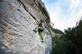A Strong Girl Climbs The Rock. Training In Rock Climbing. The Climber Climbs The Rock. Exercise In N poster