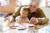 Cute Little Baby Toddler Girl And Handsome Senior Grandfather Painting With Colorful Pencils At Home poster