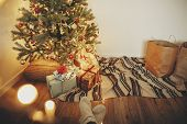 Girl Legs In Stylish Warm Sock Sitting With Garland Lights At Christmas Tree With Presents And Gifts poster