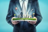 A Giant Businessman Holds An Open Book That Also Holds A Tiny Businessman Standing On A Field Near S poster
