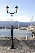 stock photo of safe haven  - Victorian lamp on quayside and marina in Calvi corsica - JPG