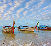 A gentle warm morning on a fabulous beach. Beautifully decorated native boats Longtails anchored awa
