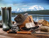 foto of fly rod  - Fly fishing equipment on deck with beautiful view of a lake and mountains - JPG