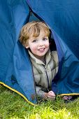 picture of boy scouts  - a young boy emerges from a tent on a camping trip - JPG