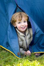 pic of boy scout  - a young boy emerges from a tent on a camping trip - JPG
