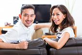 Young Indonesian couple - man and woman - sitting at home on a couch, it's weekend and they enjoying