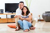 Young Indonesian couple - man and woman - sitting at home on the floor, it's weekend and they enjoyi
