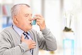 stock photo of inhalant  - Mature man treating asthma with inhaler at home - JPG
