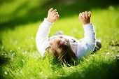 Cute happy playful baby lying alone outdoors in summer park with hands up