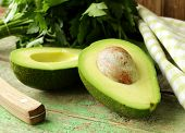 image of wooden table  - ripe avocado cut in half on a wooden table