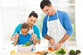 stock photo of apron  - mother teaching little daughter mixing salad when family cooking in kitchen - JPG
