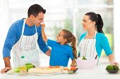 foto of feeding  - cute little daughter feeding father a piece of tomato in kitchen - JPG