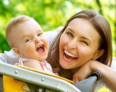 stock photo of dental  - Laughing Mother And Baby outdoors - JPG