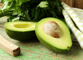 picture of half  - ripe avocado cut in half on a wooden table