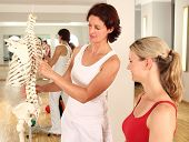 foto of spine  - Physiotherapist explaining the spine to an female patient