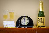 A clock showing midnight at New Year with a bottle of champagne labelled 2014, glasses and invitatio
