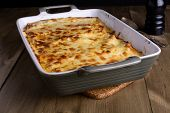 picture of lasagna  - Lasagna in a serving plate with cheese on top on an old wood table - JPG