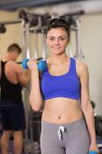 picture of lats  - Portrait of a sporty young woman with dumbbell while man using lat machine in the gym - JPG