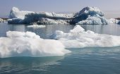 stock photo of iceberg  - Icebergs floating and glacier in the background on Jokulsarlon Iceland Southeast area - JPG